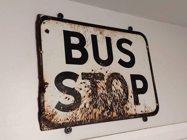 bus stop enamel sign fixed to wall
